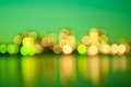 Green city lights blurred with bokeh effect reflected on water Royalty Free Stock Image