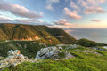 Green cliffs overlooking cabot trail the winding road seen from high above on the skyline at sunset in cape breton highlands Royalty Free Stock Photos