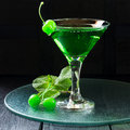 Green cocktail with maraschino cherry in a martini glass Royalty Free Stock Photo
