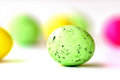 A green colored easter egg among several other blurred ones Stock Images