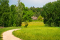 Green country area with path agriculture field and traditional village house eastern europe Royalty Free Stock Photos