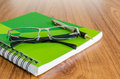 Green diary with black glasses and gold pen on wood table Royalty Free Stock Photos