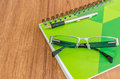 Green diary with black glasses and gold pen on wood table Royalty Free Stock Photo