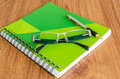 Green diary with black glasses and gold pen on wood table Stock Photos