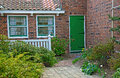 Green door brick house with Stock Photo