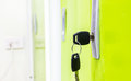 Green door with keys in lock close up of a Royalty Free Stock Photo
