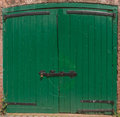 Green door lockup doors with antique wrought iron hinges and latches Royalty Free Stock Image