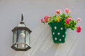 Green dotted flowerpot and pink flowers on a white wall with vintage lantern andalusian town spain Stock Image