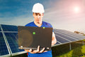 Green energy solar panels with blue sky photovoltaic system for the production of renewable through a technician standing in front Royalty Free Stock Images
