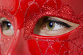 Green eyes between a red mask closeup photo of young lady with glamour Royalty Free Stock Image