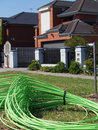 Green fiber optic cable piled in front of residential housing Royalty Free Stock Photo