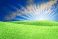 Green field blue sky white cloud and sun rays. Royalty Free Stock Images
