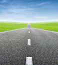 Green field and road over blue sky Royalty Free Stock Photo