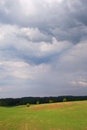 Green field under blue clouds Royalty Free Stock Images