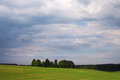 Green field under blue clouds Royalty Free Stock Photography