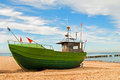 Green fishing boat on the seashore with blue sky in background Royalty Free Stock Photo