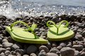 Green flip flops on the pebble beach women s Stock Photo