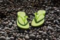 Green flip flops on the pebble beach women s Royalty Free Stock Photos
