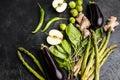 Green fresh seasonal vegetables on black table top background