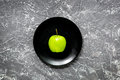 green fresh vegetables, fruits and apple on plate for healthy salad dark background top view Royalty Free Stock Photo