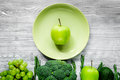 Green fresh vegetables, fruits and apple on plate for healthy salad ligth background top view Royalty Free Stock Photo