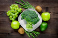 Green fresh vegetables and fruits for healthy salad on wooden table background top view