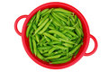 Green garden peas in red colander Royalty Free Stock Photo
