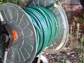Green gardening hose for watering flowers and grass wrapped around the aluminum carrier. Garden watering hose compressed. Royalty Free Stock Photo