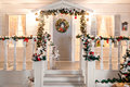 Green garlands of fir or pine branches with red and gold Christmas toys door on the veranda Royalty Free Stock Photo