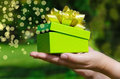 Green gift box in woman s hands on phone with light bokeh and rays Royalty Free Stock Photos