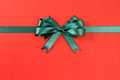 Green gift ribbon bow straight horizontal on red paper background Royalty Free Stock Photo