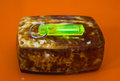 Green glowing tritium trinket on amber box Royalty Free Stock Photo