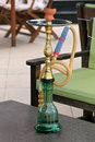 Green and gold hookah on the table of an outdoor cafe Royalty Free Stock Photography