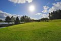 Green golf field and blue cloudy sky. european landscape Royalty Free Stock Photo