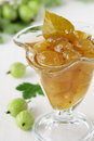 Green gooseberry jam in glass and branch Royalty Free Stock Photos