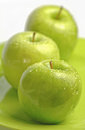 Green granny smith apples on plate Royalty Free Stock Photos