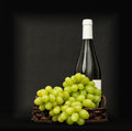 Green grapes in a basket and bottle of wine behind it on dark table Stock Photography