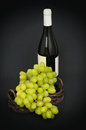 Green grapes and a bottle of wine behind it on dark table Royalty Free Stock Photography