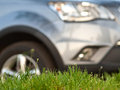 Green grass with car staying on background Royalty Free Stock Photo