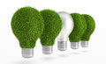 Green grass light bulb row with regular bulb in energy saving lamp concept Royalty Free Stock Photography