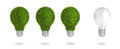 Green grass light bulb row with regular bulb in energy saving lamp concept Stock Photo