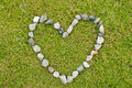 Green grass texture background with heart rock sym Stock Photos