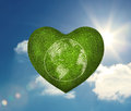 Green heart shape with earth drawn on it floating in the sky Royalty Free Stock Images