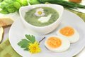 Green herbs soup with eggs and a dollop of cream Stock Photo