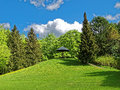 Green hill with bench under sun umbrella in park Royalty Free Stock Photo