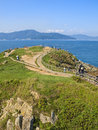 Green hill by sea with people walking along paths Royalty Free Stock Photo