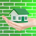 Green house in hand against brick wall background conceptual image Royalty Free Stock Photos