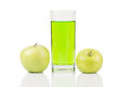 Green juice standing between two green apples with water drops on surface on white background. Royalty Free Stock Photo