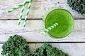 Green kale smoothie with straw overhead view on old wood Royalty Free Stock Photo