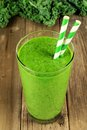 Green kale smoothie on wood background Royalty Free Stock Photo